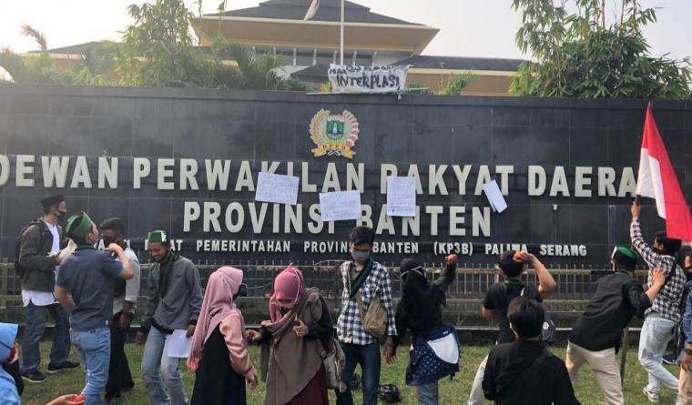 Massa aksi saat melempar tomat busuk ke depan Gedung DPRD Provinsi Banten. (Foto: TitikNOL)