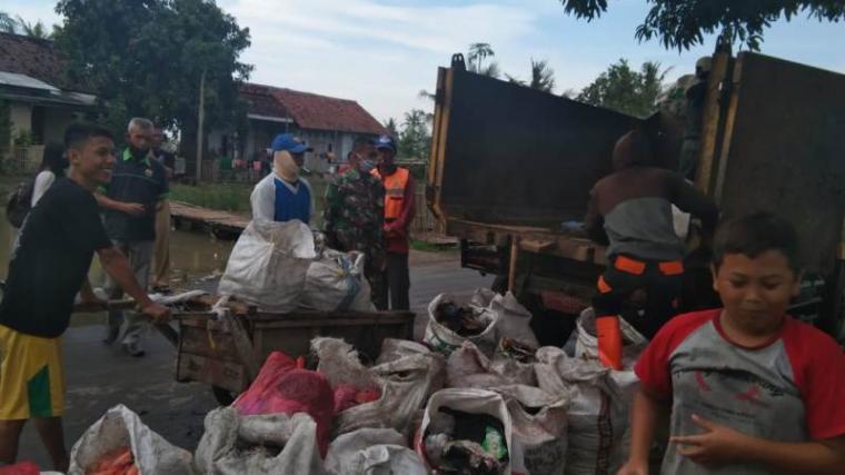 Babinsa Koramil 0202/Kasemen bersama warga saat membersihkan sampah di bantaran kali. (Foto: TitikNOL)