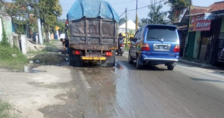 Truk pengangkut pasir basah di ruas Jalan Maulana Hasanudin, Kabupaten Lebak. (Foto: TitikNOL)