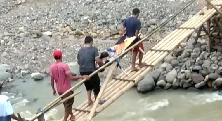 Ibu hamil yang ditandu saat melewati sungai Ciberang. (Foto: TitikNOL)