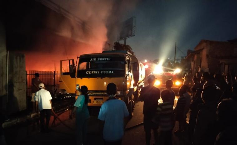 Petugas pemadam kebakaran sesang memadamkan api di bengkel yang beelokasi dibawa fly over Merak. (Foto: TitikNOL)