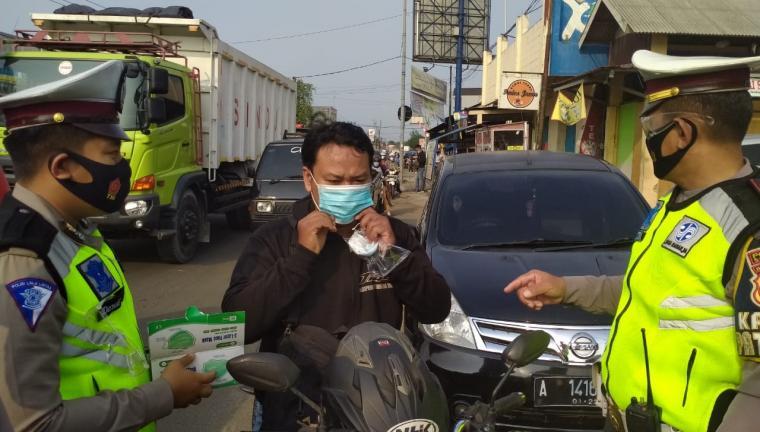 Personel Satuan Lalu Lintas (Satlantas) Polres Serang saat membagikan masker kepada pengguna jalan. (Foto: TitikNOL)
