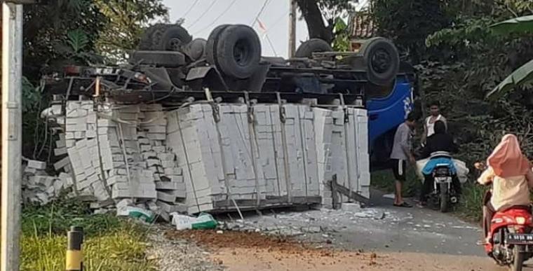 Truk bermuatan hebel yang terguling di ruas jalan raya Arif Rahman Hakim, tepatnya di Kampung Pasarkeong, Desa Pasarkeong, Kecamatan Cibadak, Kabupaten Lebak. (Foto: TitikNOL)