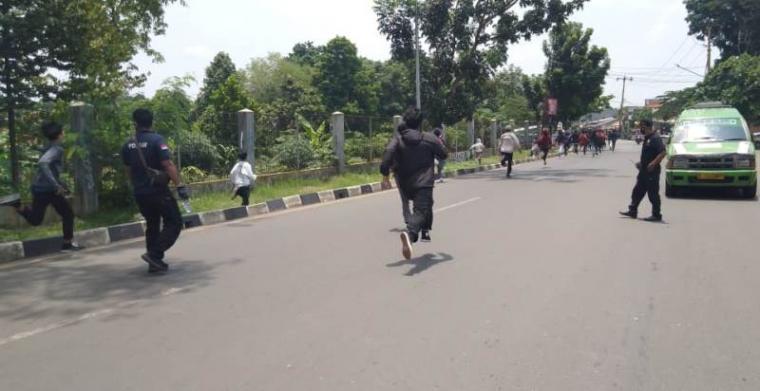 Sejumlah remaja yang diduga akan ikut aksi tolak UU Cipta Kerja di Jakarta kocar-kacir dikejar polisi, saat melintas di depan Gedung DPRD Kota Tangerang Selatan (Tangsel), Kamis (8/10/2020). (Foto: TitikNOL)