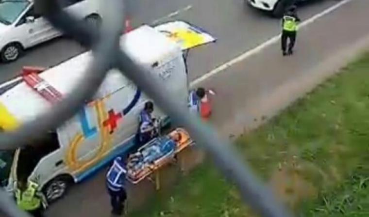 Petugas kepolisian saat mengevakuasi tubuh korban yang loncat dari jembatan. (Foto: TitikNOL)