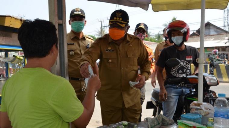 Pjs Bupati Serang Ade Ariyanto saat membagikan masker kepada pedagang. (Foto: Ist)