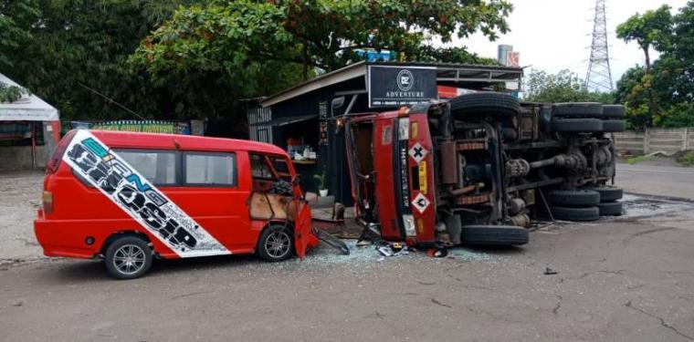 Truk tangki muatan bahan kimia terguling setelah terlibat kecelakaan dengan angkot di pintu keluar SPBU Grogol. (Foto: TitikNOL)