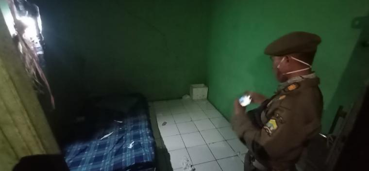 Petugas Satpol PP saat mendokumentasikan tempat tidur di salah satu toko yang diduga dijadikan tempat esek-esek. (Foto: TitikNOL)