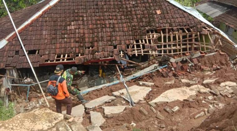 Pagar SDN 2 Muncang yang menimpa rumah salah satu warga. (Foto: TitikNOL)