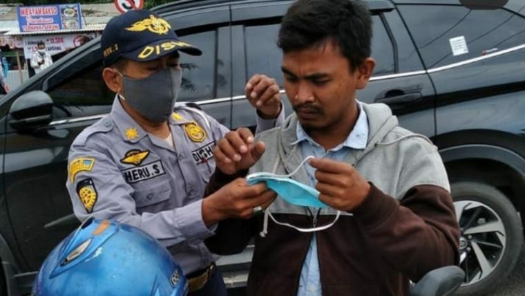 Petugas Dishub dan Satlantas Polres Cilegon saat membagikan masker kepada pengendara sepeda motor di Simpang Bojonegara. (Foto: TitikNOL)