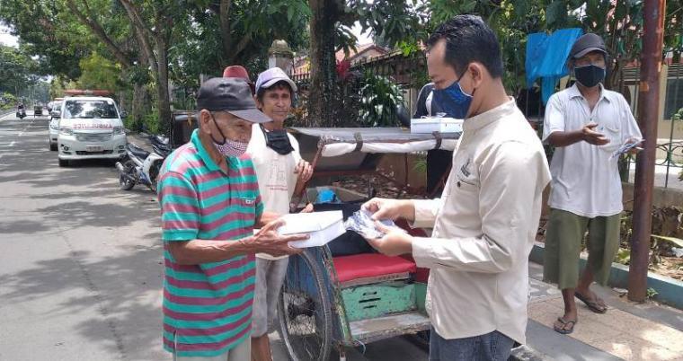 Ketua Pokja Wartawan Harian dan Elektronik Lebak Mastur Huda saat membagikan masker dan nasi bungkus. (Foto: TitikNOL)