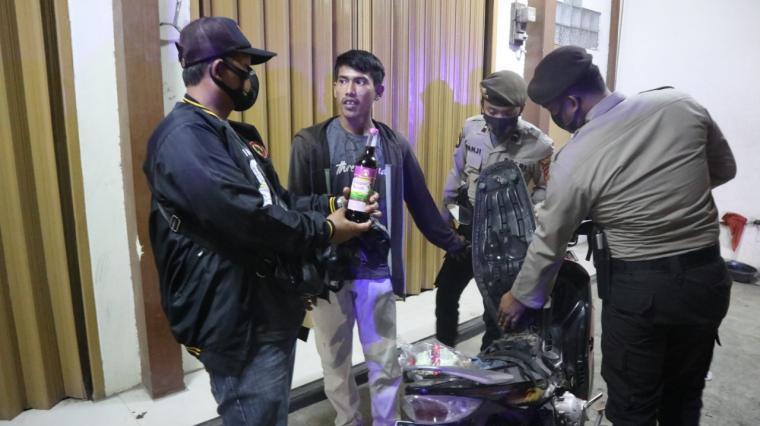 Petugas mengamankan seorang pemuda yang kedapatan membawa minuman keras. (Foto: TitikNOL)