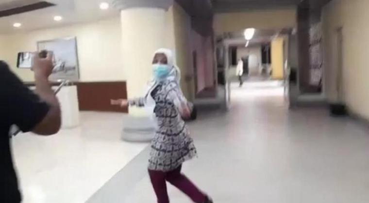 Kepala Dinkes Provinsi Banten Ati Pramudji Hastuti saat berlari menghundari awak media di gedung DPRD Banten. (Foto: TitikNOL)