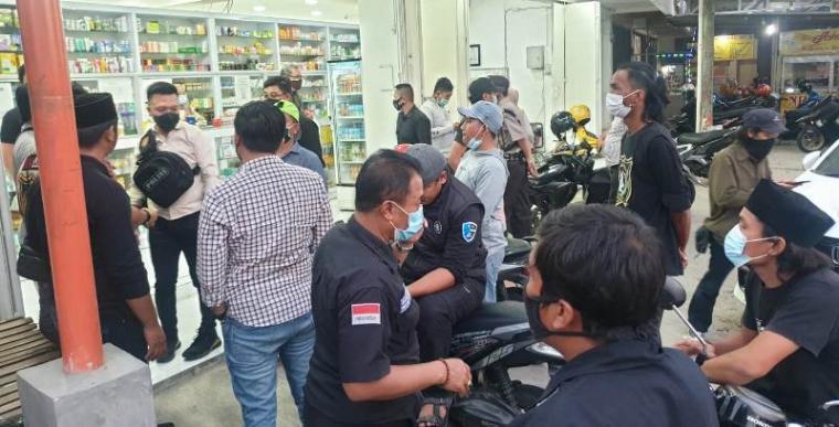 Polisi sedang berusaha menenangkan massa LSM BMPP di Apotek Gama. (Foto: TitikNOL)