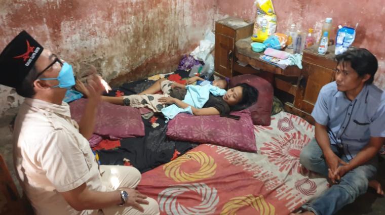 Anggota DPRD Kota Cilegon Rahmatullah saat menyambingi Dian Marisa yang mengalami lumpuh. (Foto: TitikNOL)